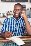 Smiling young entrepreneur talking on a cellphone in his cafe Stock Photo