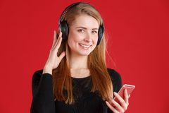 Smiling young girl, listening to music in headphones from a mobile phone and smiling. On a red background. royalty free stock photos