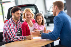 Smiling young family with car dealer Stock Photo