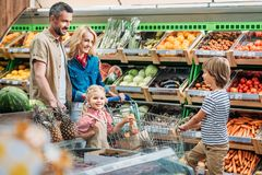 smiling young family with cart shopping together stock photos