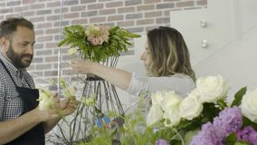 Family of two florists prepare an arrangement of flowers at flower shop. Smiling young family florists prepare flowers for wedding event in their little flower stock footage