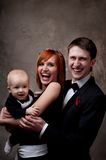 Smiling young family in formal dress Stock Image