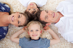 Smiling young family lying on the floor Stock Images