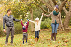 Smiling young family raising their hands. On an autumns day Stock Photos