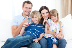 Smiling young family singing a karaoke together. In the living-room Stock Image