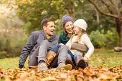Smiling young family sitting in leaves Stock Photo