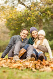 Smiling young family sitting in leaves Royalty Free Stock Image