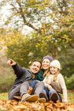 Smiling young family sitting in leaves Stock Image