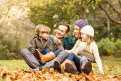 Smiling young family sitting in leaves Royalty Free Stock Photo