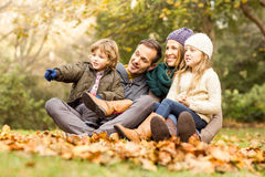Smiling young family sitting in leaves Stock Photos
