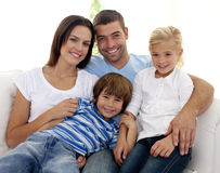 Smiling young family sitting on sofa Stock Images