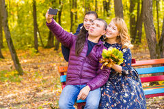 Smiling young family taking selfies on an autumns day Stock Photos