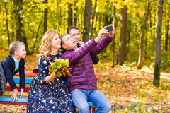 Smiling young family taking selfies on an autumns day Royalty Free Stock Photo