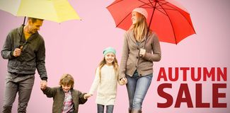 Composite image of smiling young family under umbrella. Smiling young family under umbrella against pink background royalty free stock image