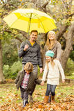 Smiling young family under umbrella Royalty Free Stock Photo