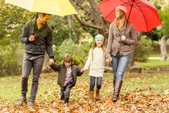 Smiling young family under umbrella Royalty Free Stock Photos