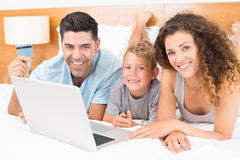 Smiling young family using laptop to shop online together on bed Royalty Free Stock Image