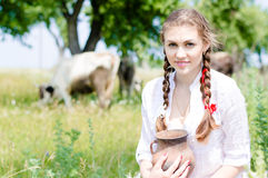 Smiling young farmer carrying bowl of fresh milk Stock Image