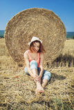 Smiling young farmer woman leans the haystack during harvest by Stock Images