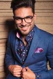 Smiling young fashion man closing his jacket Stock Images