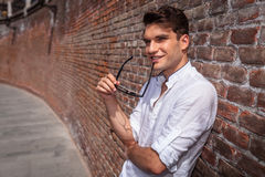 Smiling young fashion man holding his glasses in his hand. Royalty Free Stock Photo