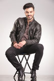 Smiling young fashion man sitting on a chair Stock Images