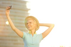 Smiling young fashion woman with hat taking selfie Royalty Free Stock Photos