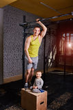 Smiling young father and little son standing on the box against brick wall at the cross fit gym. Stock Photo