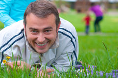Smiling young father lying in the grass Stock Images