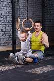 Smiling young father trains the little son with gimnastic rings against brick wall in the gym. Royalty Free Stock Photos