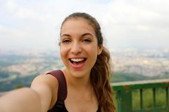 Smiling young female backpacker take self portrait on Pico do Jaragua with Sao Paulo metropolis skyline on the background, Brazil royalty free stock photos