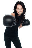 Smiling young female boxer ready to punch you Stock Photography