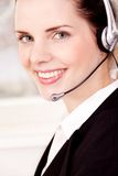 Smiling young female callcenter agent with headset Royalty Free Stock Photos
