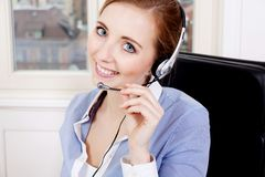 Smiling young female callcenter agent with headset Stock Image