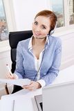 Smiling young female callcenter agent with headset Stock Photography
