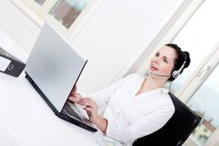 Smiling young female callcenter agent with headset Royalty Free Stock Images