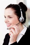 Smiling young female callcenter agent with headset Royalty Free Stock Photography