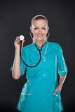 Smiling young female doctor in green uniform. Stock Image