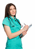 Smiling young female doctor in uniform with clipboard writing Stock Photo