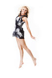 Smiling young female in dress jumping Royalty Free Stock Photography