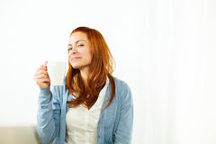Smiling young female enjoying a caffee cup Royalty Free Stock Photos