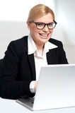 Smiling young female executive at work desk Royalty Free Stock Photo