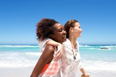 Smiling young female friends at the beach Royalty Free Stock Image