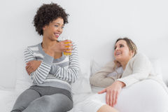 Smiling young female friends chatting in bed Royalty Free Stock Photography