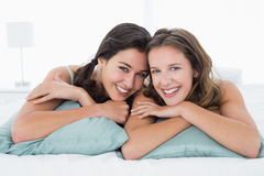 Smiling young female friends lying in bed Royalty Free Stock Image