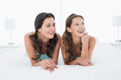 Smiling young female friends lying in bed Royalty Free Stock Photography