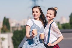 smiling young female friends with paper cups of coffee royalty free stock photos