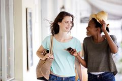 Smiling young female friends walking and talking Royalty Free Stock Photography