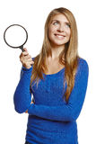 Smiling young female holding magnifying glass Royalty Free Stock Photos