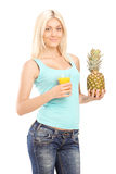 Smiling young female holding pineapple and orange juice Royalty Free Stock Photography